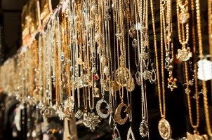 A seemingly endless collection of gold necklace pendants hanging in an open market
