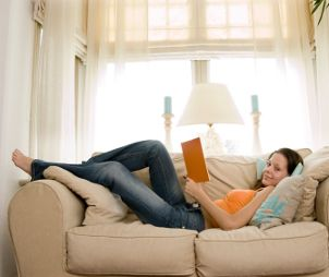 Woman wearing jeans and reading on the couch
