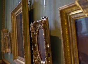 Gallery of ornately framed art hanging at varying heights