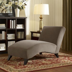 Tan chaise lounge sits beside bookshelf and brass table lamp