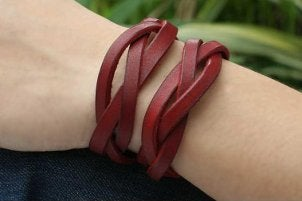 A woman wearing two red braided leather bracelets