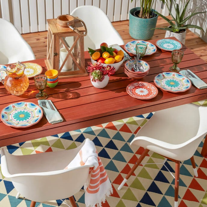 Beautifully decorated outdoor dining space with color kitchen decor and patterned outdoor area rug only at Overstock.com