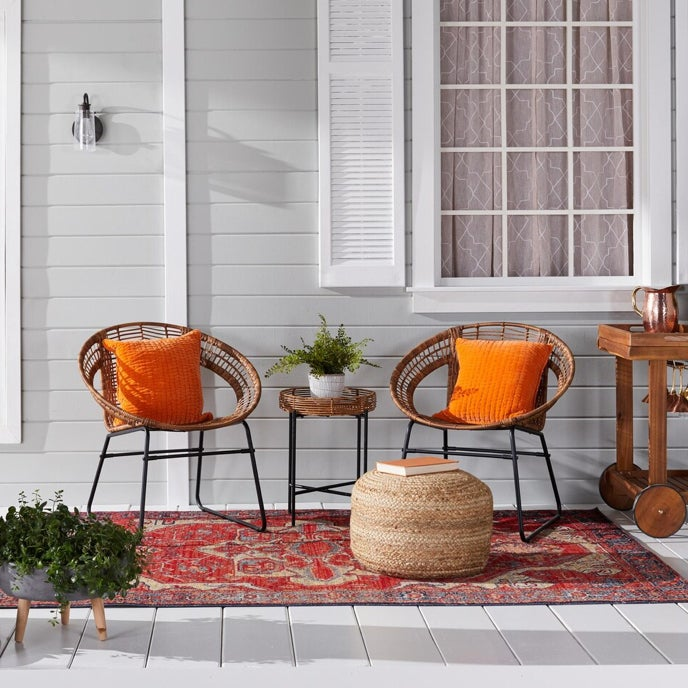 A pair of round wicker chairs on the front porch of a light grey home with orange throw pillows available at Overstock